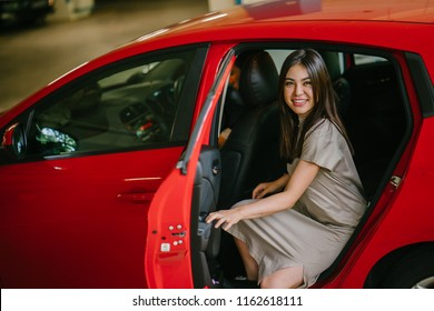 Portrait of a young and attractive Japanese Asian woman exiting and getting out of her private car that she booked from a hailing app on her phone at her destination. She is smiling happily.