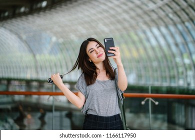 Portrait of a young and attractive Japanese Asian tourist wearing comfortable clothing in a modern and spacious mall. She is taking a selfie and smiling as she snaps a photo of herself.