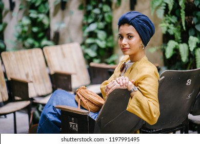 Portrait of a young and attractive Malay Muslim woman wearing a turban (hijab, head scarf). She is lounging on a wooden chair in a trendy cafe during the day and is wearing a stylish outfit.