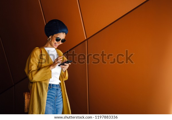 Portrait of a young and attractive Malay Muslim woman using her smartphone. She is tall, elegant and is wearing a turban (hijab, head scarf). She is smiling as she uses her smartphone.