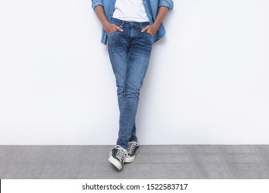 portrait of a young attractive man in blue jeans shirts with blue torn jeans with sneakers posing in the studio.