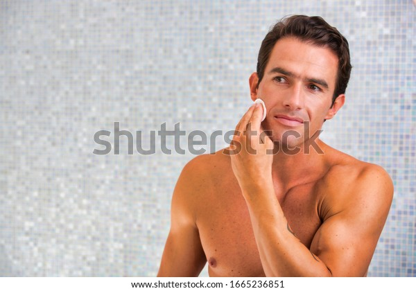 Portrait of young attractive man cleansing his face with cotton and toner in the bathroom