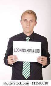 Portrait of a young attractive man holding a sign looking for a job.
