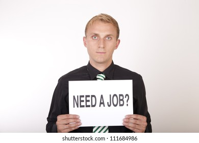 Portrait of a young attractive man holding a sign need a job?.