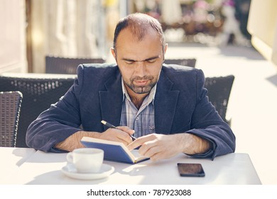 Portrait of young attractive man sitting in cafe and reading book.