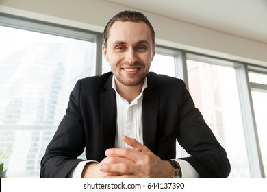 Portrait of young attractive man in suit sitting at desk looking in camera with smile. Businessman feels positive emotions during negotiations with partners. Boss on interview with job applicants