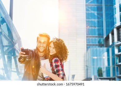 Portrait of young attractive man taking selfie with his girlfriend in the middle of the city with yellow lens flare in background