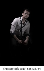 Portrait of young, attractive man in unbuttoned, creased white shirt with rolled up sleeves and loose tie sitting in the dark