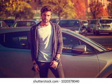 Portrait of young attractive man in white shirt leaning on his new stylish polished car outdoor in city street