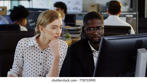 Portrait of young attractive man and woman business co-workers working on their startup project on the computer. Modern office and employees on blurred background. Indoors