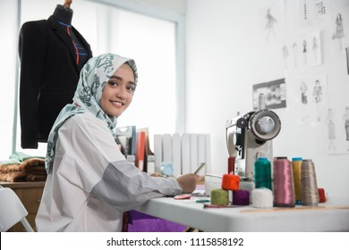 portrait of young attractive muslim woman fashion designer in her workshop smiling to camera