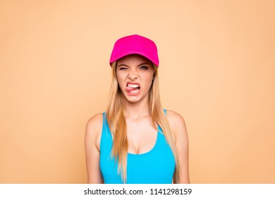 Portrait of young attractive nice cute straight-haired blonde grimacing girl wearing bright pink sunhat, showing tongue out. Isolated over beige background