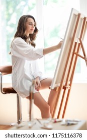 Portrait of a young attractive painter drawing on canvas in art studio