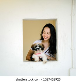 Portrait of a young and attractive young Pan Asian girl with her pet shih tzuh dog. She is smiling and holding her dog and peeking through a square window in the day.