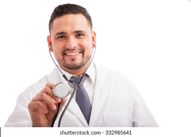 Portrait of a young attractive pediatrician using a stethoscope against a white background and smiling
