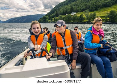 Portrait of young and attractive people, friends in the motorboat driving somewhere on a picnic. Happy faces, having fun, Norway.
