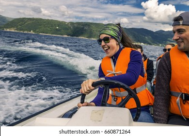 Portrait of young and attractive people, friends sitting in the motorboat close up. Girl is having fun driving the boat. You can see waves on background. Norway.