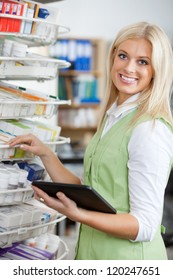 Portrait of young attractive pharmacist using digital tablet to fill order