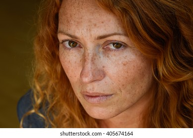 portrait of young attractive red hair woman without makeup thinking about problems close up
