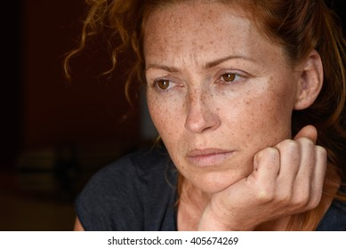 portrait of young attractive red hair woman without makeup holding chin with hand thinking about problems and looking away close up