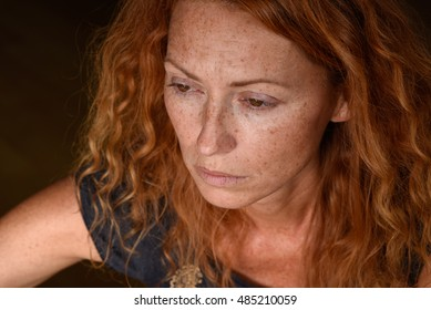 portrait of young attractive red hair woman without makeup looking down away and thinking about problems close up negative expression