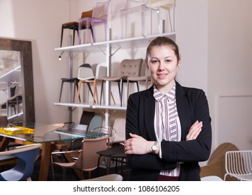 Portrait of young attractive saleswoman standing in interior of chair store