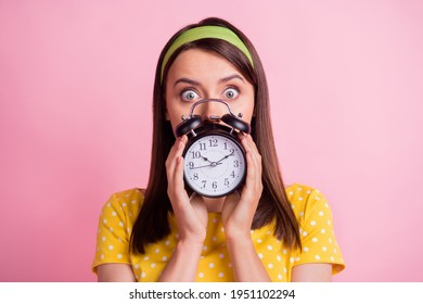 Portrait of young attractive shocked amazed surprised girl staring camera cover face hold clock isolated on pink color background