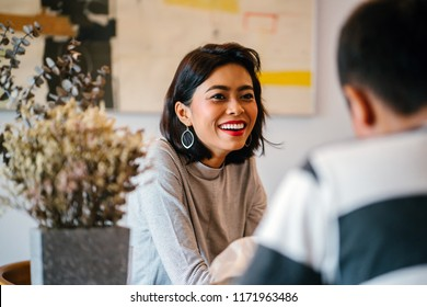 Portrait of a young and attractive Singaporean Malay woman enjoying a hot coffee beverage while she talks to a man in a living room during the day. She is smiling as she talks.
