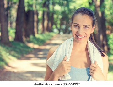 Portrait young attractive smiling fit woman with white towel resting after workout sport exercises outdoors on a background of park trees. Healthy lifestyle well being wellness happiness concept