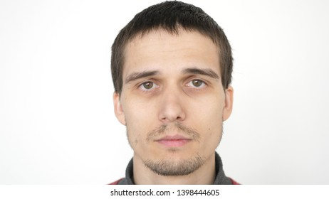 Portrait of young attractive upset man looking at the camera on a white background.