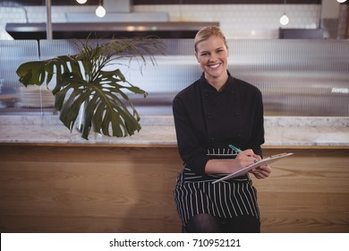 Portrait of young attractive waitress sitting with clipboard at coffee shop