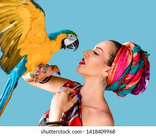 Portrait of young attractive woman in african style holding ara parrot on her hand onblue background
