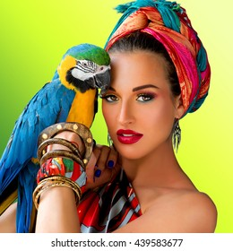 Portrait of young attractive woman in african style with ara parrot on her hand on colorful background