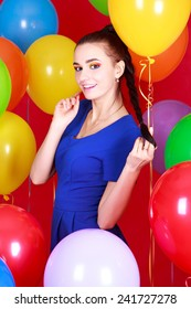 Portrait of a young attractive woman among many bright balloons over red background