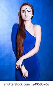 Portrait of a young attractive woman with a blue face art over dark blue background in cold colors