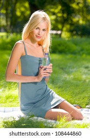 Portrait of young attractive woman with bottle of water, outdoors