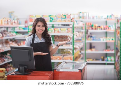 portrait of young attractive woman at cash register in a store welcoming customer