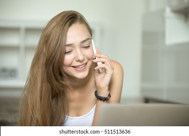 Portrait of a young attractive woman in a casual wear talking on a phone, laptop in front, home interior. Business, education concept photo, lifestyle