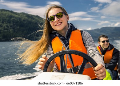 Portrait of young and attractive woman close up driving the motorboat, Norway. Beautiful, ruffled hair.