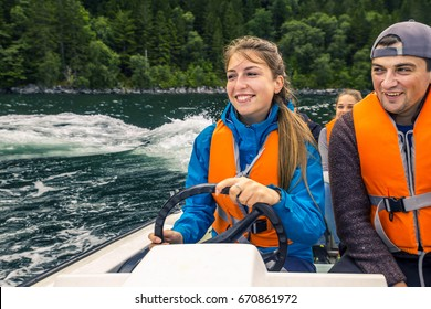 Portrait of young and attractive woman close up driving the motorboat, Norway. She is enjoying the sunny day.