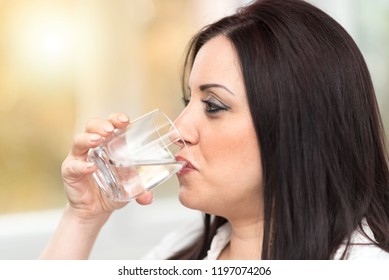 Portrait of young attractive woman drinking water