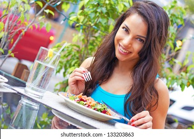 Portrait of a young attractive woman eating salad at cafe table. Horizontal shot.Beautiful young female enjoying a fresh salad at a nice restaurant. Cute hispanic girl eating a healthy meal.