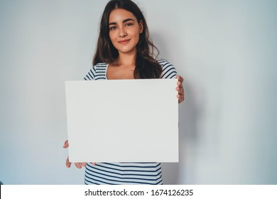 Portrait of young attractive woman holding blank paper against white background, hipster girl holding blank ad poster with copy space for text message about feminism or Save Environment Poster