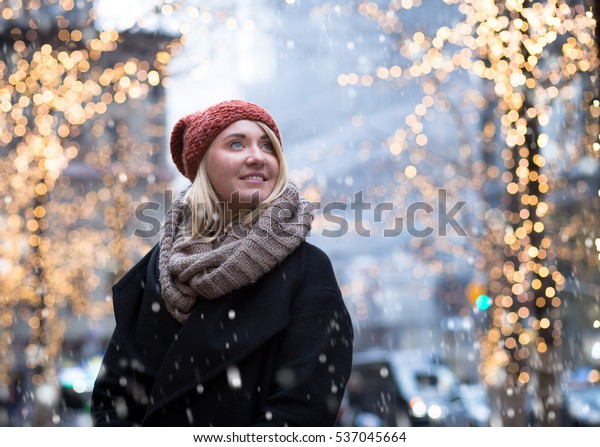 Portrait of young attractive woman with holiday lights in snowy day, photographed in NYC in December