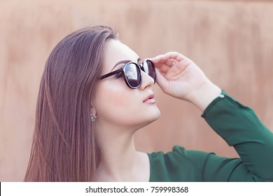 Portrait of an young attractive woman with long brown hair in sunglass on the nature with rustic wall in background