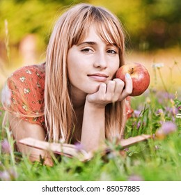 Portrait of young attractive woman lying in grass, reading book and holding apple at summer green park.