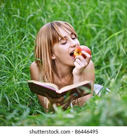 Portrait of young attractive woman lying in grass, reading book and eating apple at summer green park.