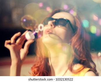 Portrait of  a young attractive woman making soap bubbles