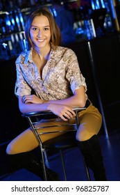 Portrait of young attractive woman in night club with a drink