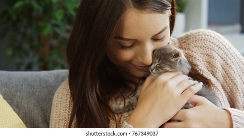 Portrait of young attractive woman in a pink sweater caressing a small kitty in her hands while sitting in the cozy room at home. Indoor. Close up